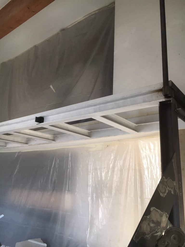 Projet d'extension d'une mezzanine avec un sol en verre et création d'un escalier métallique avec des marches en bois. Réalisation à Cannes la Bocca - Mezzanine